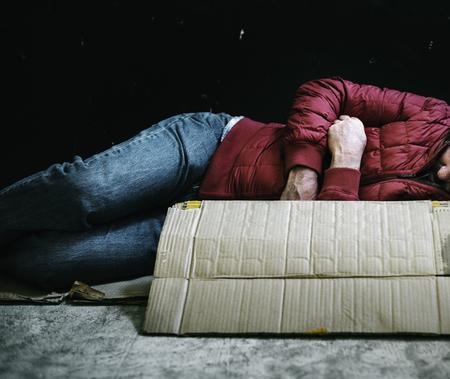 Hombre descansando sobre cartón Foto de archivo
