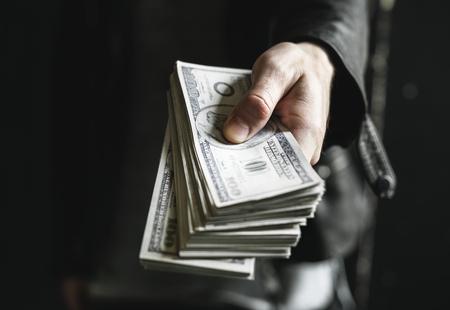 Hand holding dollar bills