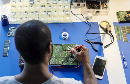 Technician using multimeter with computer electronics parts
