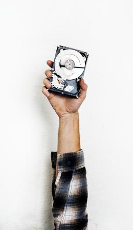 Hand, die Festplattenlaufwerk des Computers lokalisiert auf Weiß hält Standard-Bild - 85321347