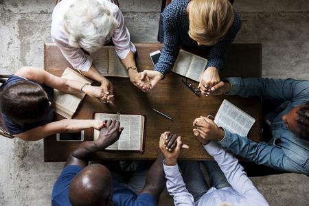 Groep mensen hand in hand bidden aanbidding geloven Stockfoto