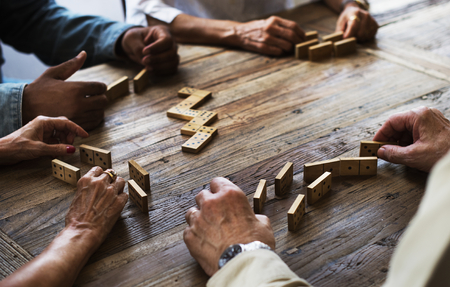 Group of people playing domino game on wooden table Stock Photo