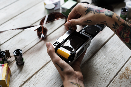 Hands with tattoo installing filmstrip to a camera