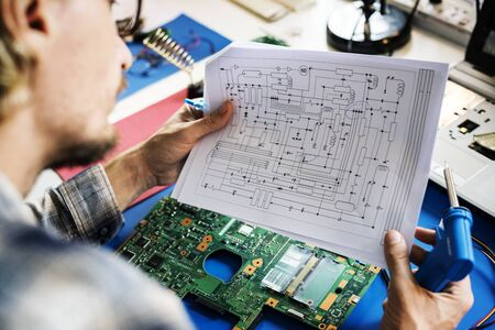 Technicians working holding electronics circuit guide paper