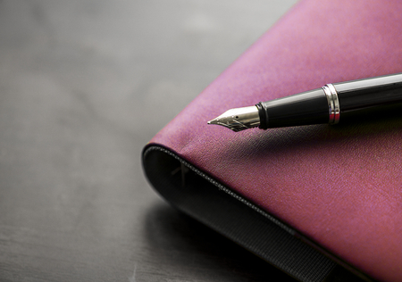 Macro of fountain pen on black notepad