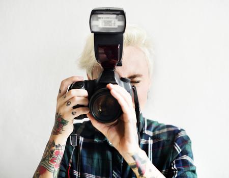 스냅 샷을 찍는 카메라를 들고 문신 캐주얼 금발의 여자 스톡 콘텐츠