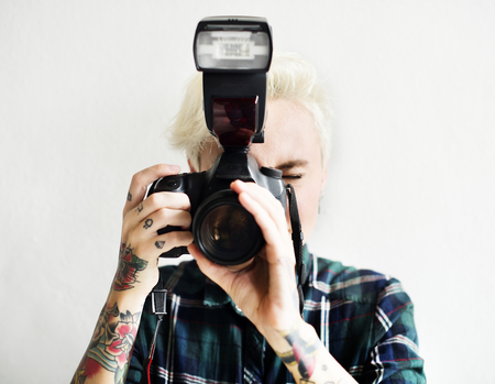 Casual blonde woman with tattoo holding camera taking a snap shot
