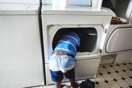 African descent kid helping mom doing the laundry Stock Photo