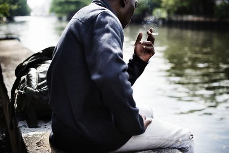 Homme d'ascendance africaine assis au bord de la rivière