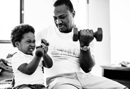 Black father enjoy exercise with his child together happiness grayscale Banco de Imagens