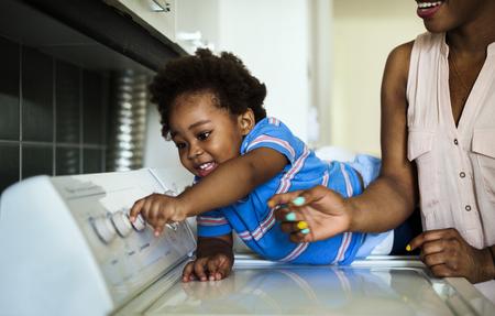 enfant ascendance africaine aidant maman faisant le linge