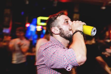 男と長時間露光を用いた夜間のビールのクローズ アップ 写真素材