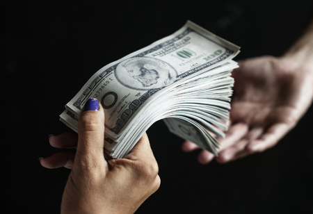 Hand passing a money to others hand Stock Photo
