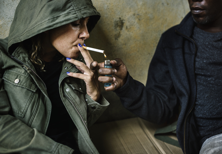 Homeless sharing a cigarette to others