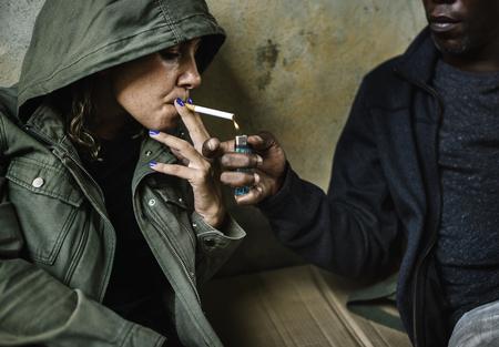 Sans-abri partageant une cigarette avec d'autres