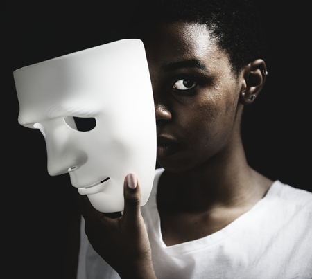 Black woman holding white mask Banque d'images