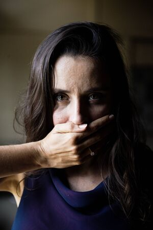 Woman with hand covered over her mouth Banque d'images