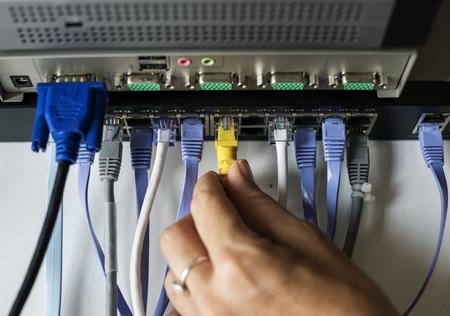 ハブに LAN ケーブルを持っている手
