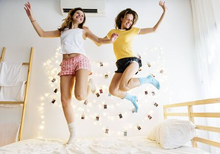 Caucasian women jumping on the bed together