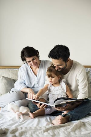 Caucasian family reading fairy tales to they daughter with happiness