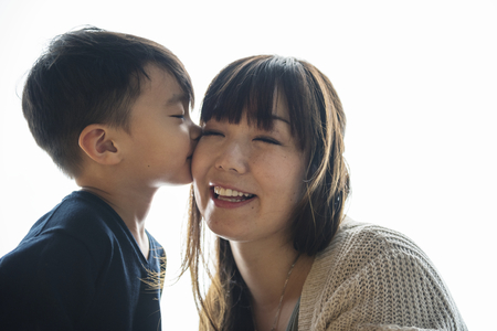 Son kissing cheek his mom with love