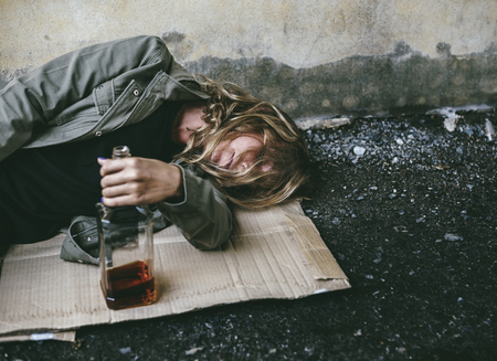 Homeless woman lay down on the ground holding alcohol