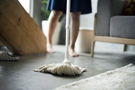Woman cleaning home with mop