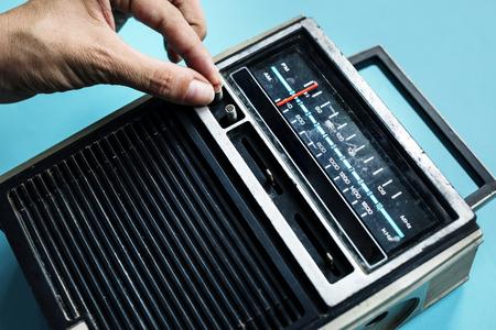 古典的なレトロなラジオのトランジスタをチューニングの手のクローズ アップ 写真素材