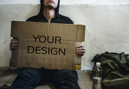 Homeless holding a placard showing a message Stock Photo
