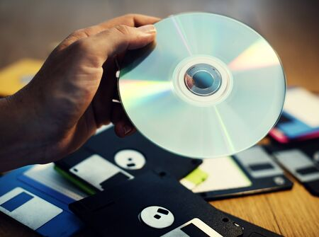 Hand holding CD disk background with floppy on the table