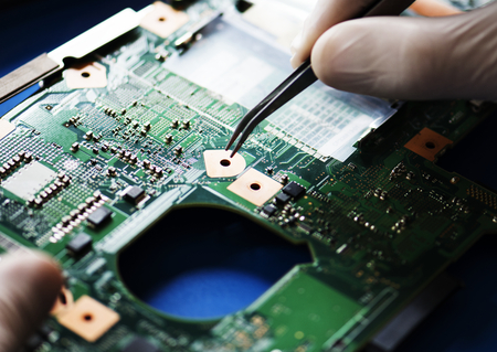 Close-up van handen met computermotherboard en pincet Stockfoto
