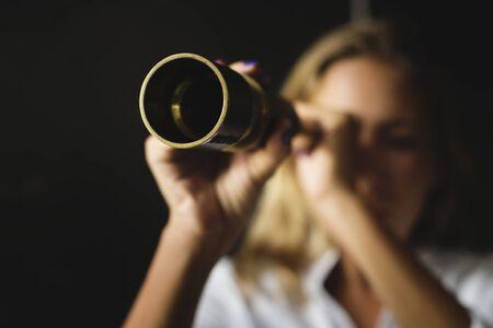 Caucasian woman using telescope spyglass Standard-Bild