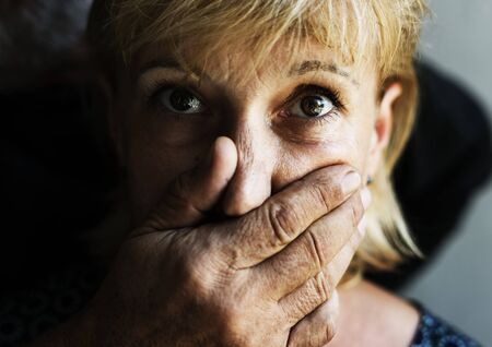 Closeup of caucasian woman face covered with somone hand