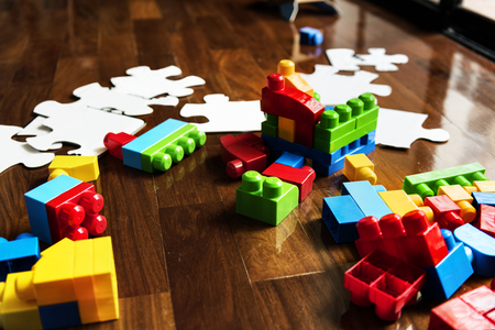 Plastic blocks and jigsaw puzzle toys on wooden floor