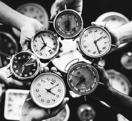 Closeup of hands holding clocks