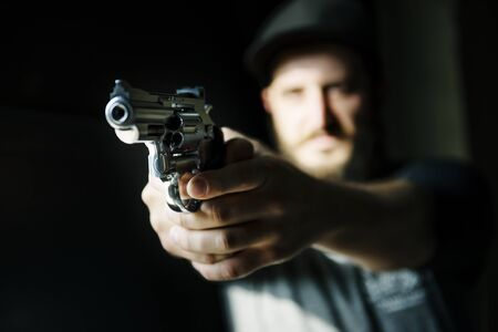 犯人の男は銃を指しています。 写真素材