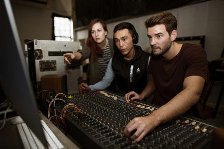 サウンド エンジニア チームは、ミキサーで音を確認します。 写真素材