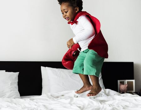 African descent kid jumping on the bed with robe 版權商用圖片