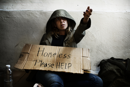 Homeless woman holding helping board on the street
