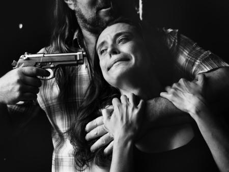 여자 머리에 총을 사용하는 사람 스톡 콘텐츠