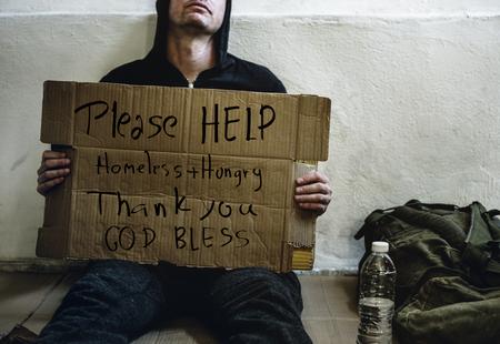 Homme sans-abri tenant tableau d'aide dans la rue
