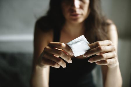 Vrouw met condoom met depressieve bezorgde gezichtsuitdrukking