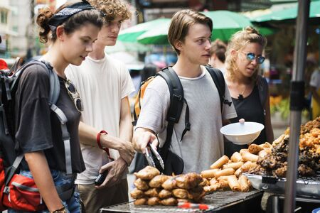 Group of tourists buying Thai Food at food stall