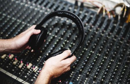 Hand with headphone ona sound mixer