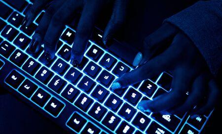 暗闇でキーボード上の手 写真素材