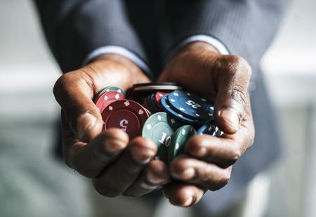 Handen met casino munten Stockfoto