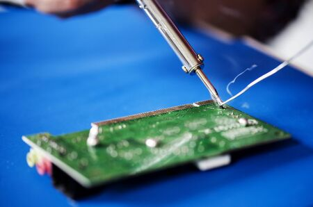 Closeup of tin soldering with electronics circuit board Banco de Imagens