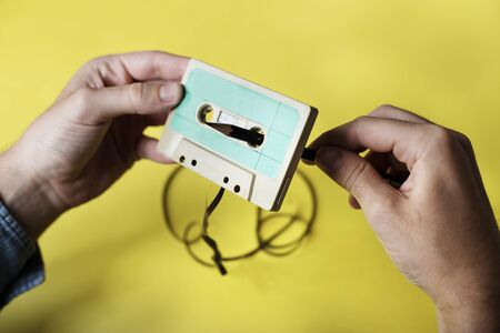 Hands holding a tape cassette rolling back