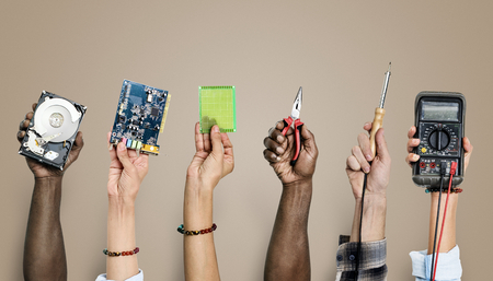 Group of hands holding computer electronics parts on brown background