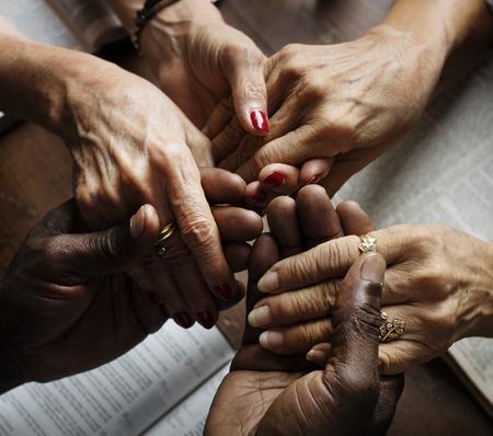 信じて礼拝を祈って手を繋いでいる人々 のグループ 写真素材